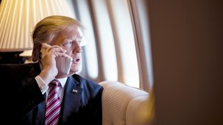 President Donald Trump talks on the phone aboard Air Force One d