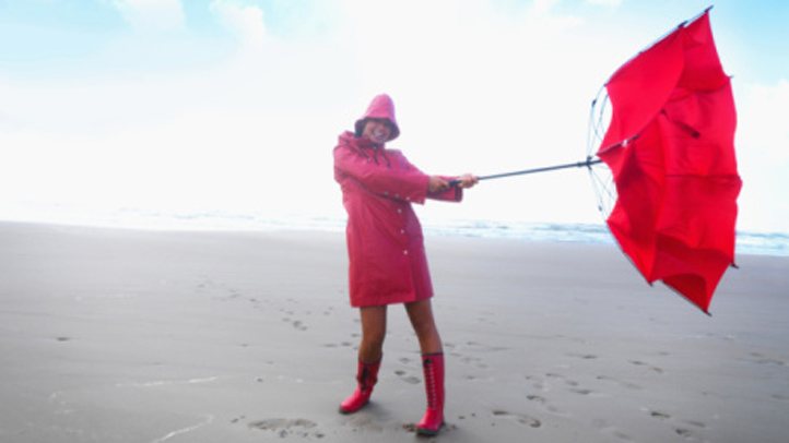 Windy day - Young female in red raincoat on the sea shore