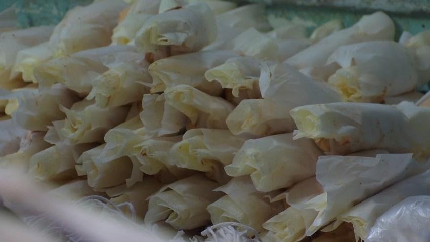 Employees at Las Cuatro Milpas in Barrio Logan prepare tamales for customers.