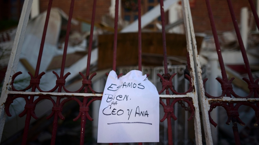 """A note that reads """"We're well. Ceo and Ana,"""" hangs on a fence"""