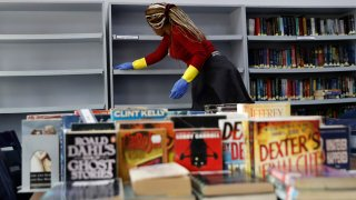 A worker disinfects bookshelves at the library of the Evangelical School, in Loueizeh, east of Beirut, Lebanon, Monday, March 2, 2020.