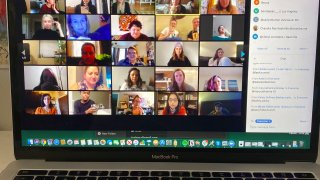 A laptop shows people gathered together online for a virtual happy hour