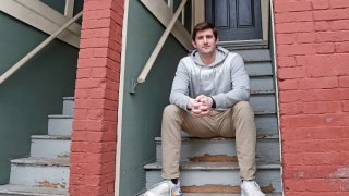 """Cameron Karosis, 27, a software salesman, poses for a portrait outside his home, Tuesday, April 14, 2020, in Cambridge, Mass. Karosis usually strives to protect his personal information. But a scary bout with COVID-19 that began with headaches and fevers, progressed to breathing problems and led to a hospital visit has now left him eager to disclose as much as possible to help halt the virus' spread. """"I'm sick and I'm under a quarantine -- hold me accountable for it,"""" he said. """"You have the potential to kill other people."""""""
