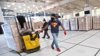 Workers unload pallets stacked with boxes of prepared meals that will be distributed to people in need, Thursday, April 30, 2020, at a temporary food distribution center at Basketball City on Pier 36 in New York.