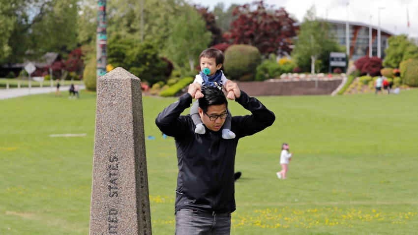 In this photo taken Sunday, May 17, 2020, Bryan Albano, walks with his son Zachary atop his shoulders in Canada at Peace Arch Provincial Park, adjacent to Peace Arch Historical State Park on the U.S. side, where people can walk freely between the two countries at an otherwise closed border, in Blaine, Wash.
