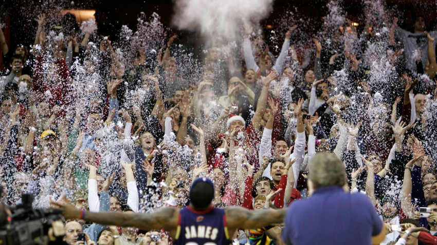 In this Dec. 25, 2008, file photo, fans toss confetti to mimic Cleveland Cavaliers' LeBron James's pre-game chalk toss before an NBA basketball game against the Washington Wizards in Cleveland. Billions has been spent on state-of-the-art sports facilities over the last quarter-century, but there is no way to prevent the potential spread of a virus through coughing or sneezing. Officials are working on safety protocols and looking at new technology in hopes of making stadiums and arenas as safe as they can.