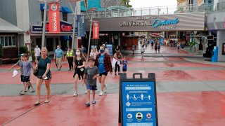 Signs about social distancing and other protocols are seen about the theme park as guests walk by at Universal Orlando Resort