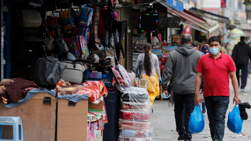 Shoppers walk past opened retail shops as coronavirus restrictions on non-essential retailers were lifted in London, Friday, June 19, 2020.