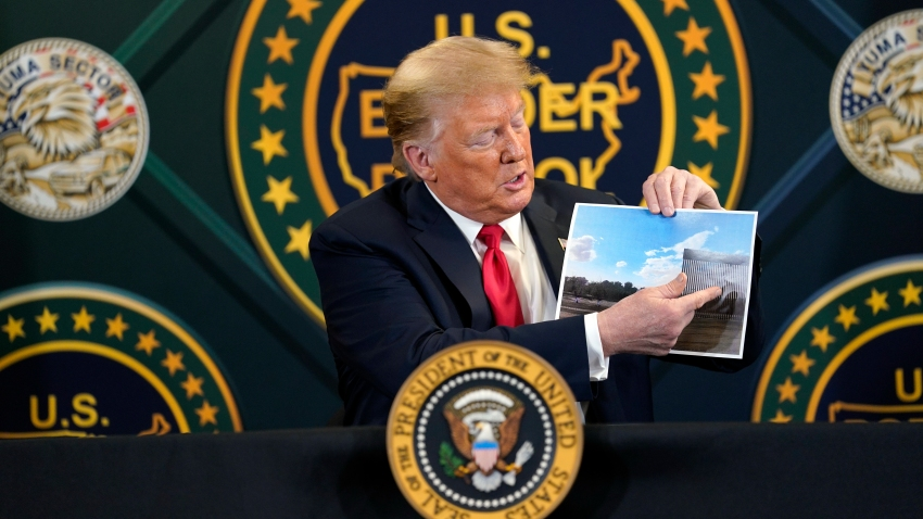 President Donald Trump holds an image of the U.S. border wall