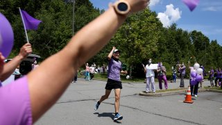 Nursing home workers cheer as Corey Cappelloni completes his seventh ultramarathon in seven days in Scranton, Pa.