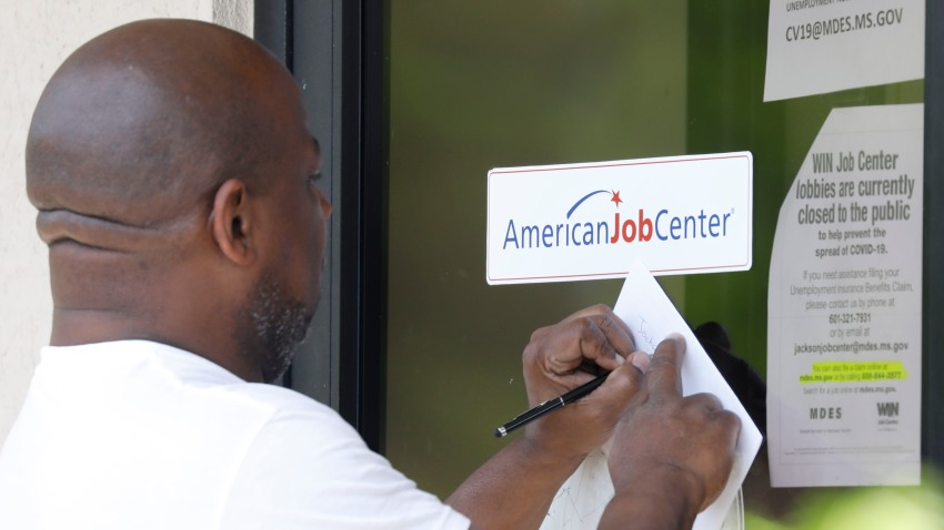 In this April 2, 2020, file photo, a resident copies down the Mississippi unemployment benefit website after being unable to enter the state WIN Job Center in north Jackson, Miss.