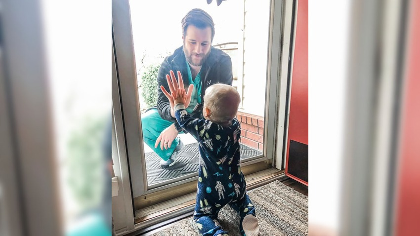 Dr. Jared Burks, sees his 1-year-old son crawl for the first time, as he touches a glass door from the outside while their son Zeke touches it from the inside of their Jonesboro, Ark.