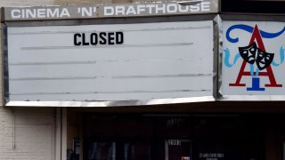 A woman wearing a face mask walks past the closed Arlington Cinema and Drafthouse movie theater amid the coronavirus pandemic on May 14, 2020, in Arlington, Virginia.
