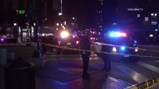 Picture of the scene showing police, police cars and caution tape near a 7-Eleven in Downtown San Diego