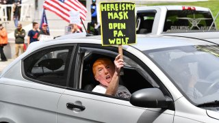 """A car passenger disguised behind a Trump mask wields a sign as part of a """"reopen"""" Pennsylvania demonstration on April 20, 2020, in Harrisburg, Pennsylvania."""