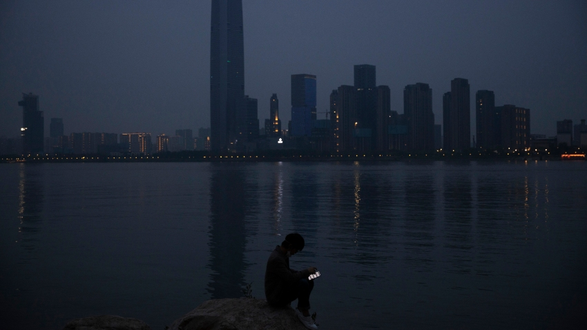 In this April 5, 2020, file photo, a man checks his mobile phone along the Yangtze River in Wuhan in central China's Hubei province. As governments around the world consider how to monitor new coronavirus outbreaks while reopening their societies, many are starting to bet on smartphone apps to help stanch the pandemic.