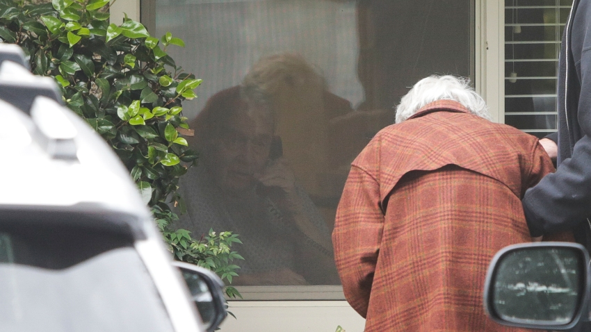 Charlie Campbell a retired RN from Silver City, New Mexico, takes his mom Dorothy Campbell, 88, of Bothell to see her husband Gene Campbell, 89, through his room window on March 5, 2020 at the Life Care Center nursing home in Kirkland, Washington where multiple cases of COVID-19 have been linked and some patients have died.