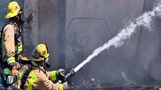 Firefighters douse wildfire.