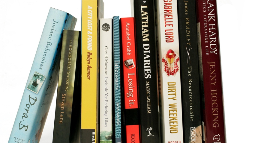 Books stand vertically on a bookshelf.