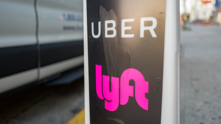 Close-up of vertical sign with logos for ridesharing companies Uber and Lyft, with wheels of a car in the background, indicating a location where rideshare pickups are available in downtown Los Angeles, California, October 24, 2018.