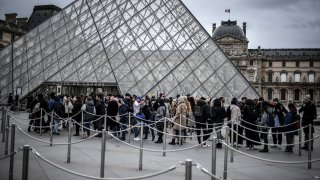 People queue at the Louvre museum.