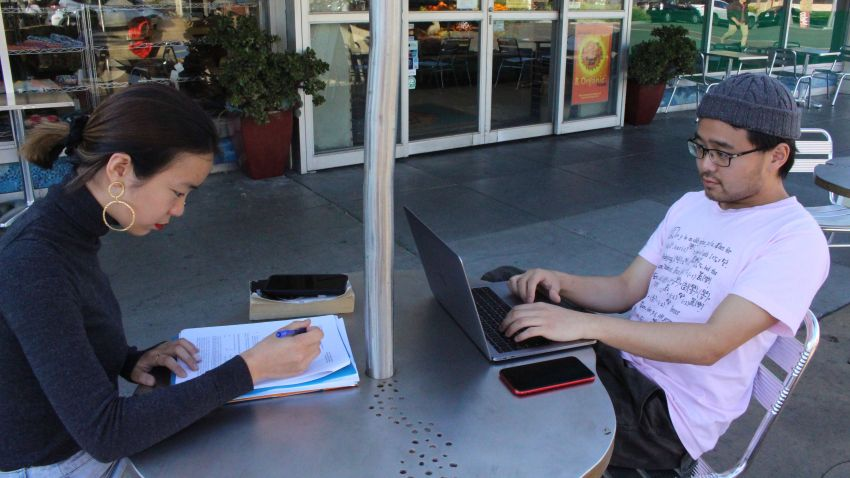 """International students Yaqing """"Victoria"""" Yang and Ende Shen of China study together at a sidewalk table in the Silicon Valley city of Palo Alto"""