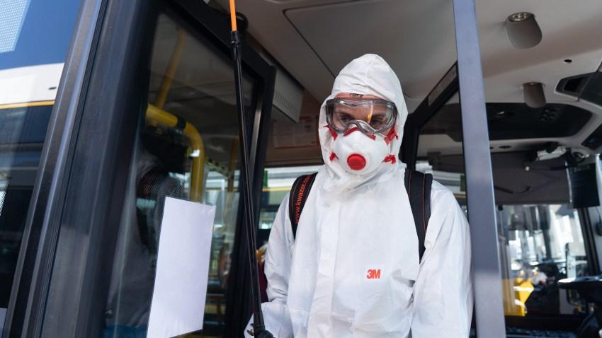 A sanitation worker disinfects public transportation