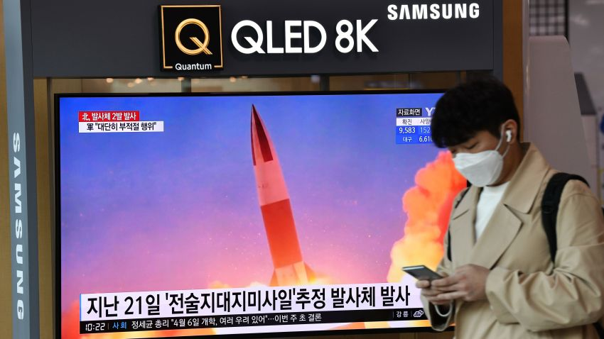 A man walks past a screen showing file footage of a North Korean missile test