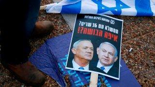A folded Israeli flag lies near a placard left on the street