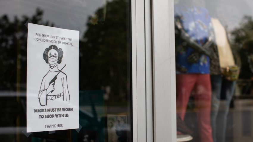 A sign asking patrons to wear a mask while shopping hangs in the window of a store in the Plaza Midwood neighborhood of Charlotte, North Carolina, U.S., on Friday, May 8, 2020.