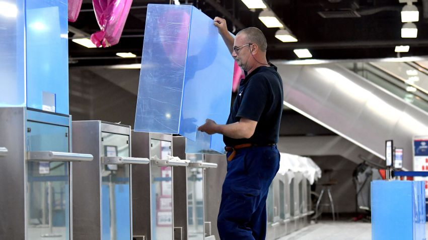 An employee installs plexiglass shields on check-in counters at Sarajevo International Airport on May 19, 2020.