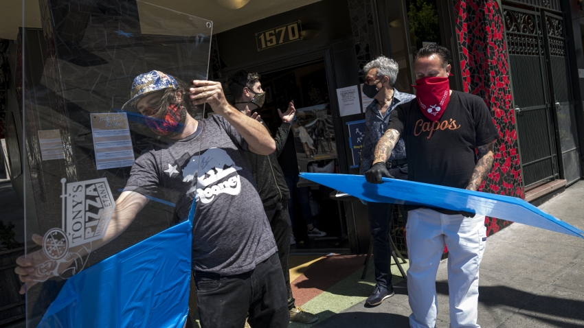 Viral Guard System workers wearing protective masks deliver plexiglass counter-top shields to a store in San Francisco, California, U.S., on Friday, May 29, 2020. Global plexiglass production increased substantially in March and April compared to February, according to ICIS, CNBC reported.