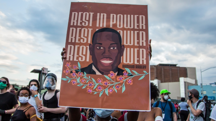 In this May 30, 2020, file photo, a protester holds a George Floyd placard during the protest in response to the death of African American George Floyd at the hands of Minneapolis, Minnesota in the Brooklyn borough of New York City.