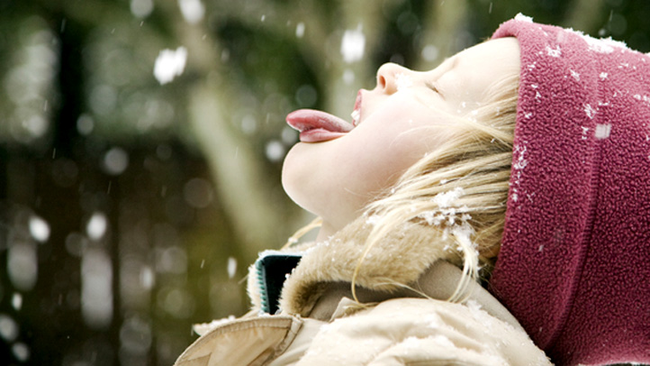 Girl catches snow on her tongue