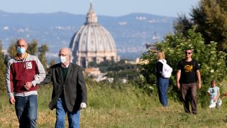 People walk at the 'Pineto' park with St. Peter's basilica in the background on the first day after Italy lifted its lockdown, May 4, 2020, in Rome. Italy was the first country to impose a nationwide lockdown to stem the transmission of the coronavirus, and its restaurants, theaters and many other businesses remain closed.