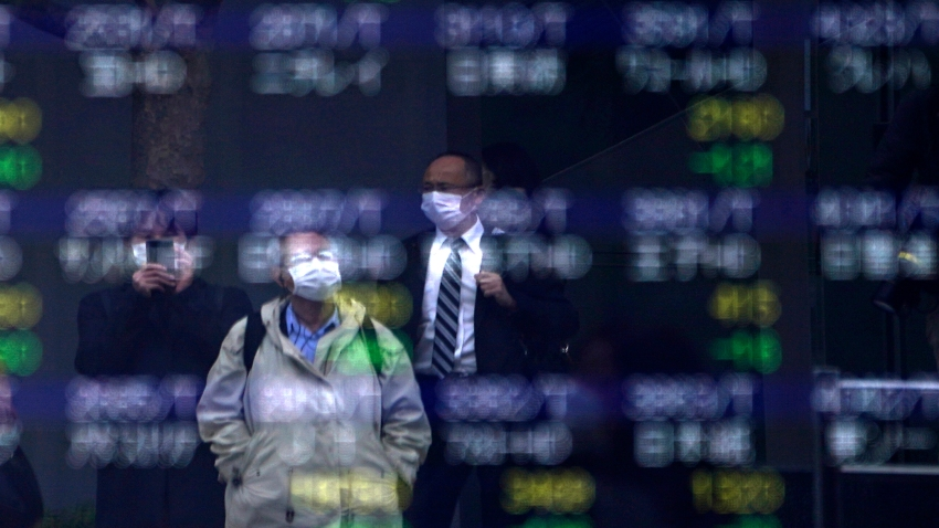 In this March 13, 2020, file photo, people are reflected on an electronic stock board showing Japan's Nikkei 225 index at a securities firm in Tokyo.