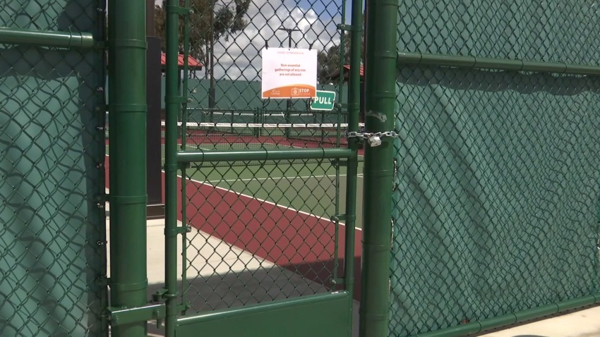A locked gate to a tennis court.