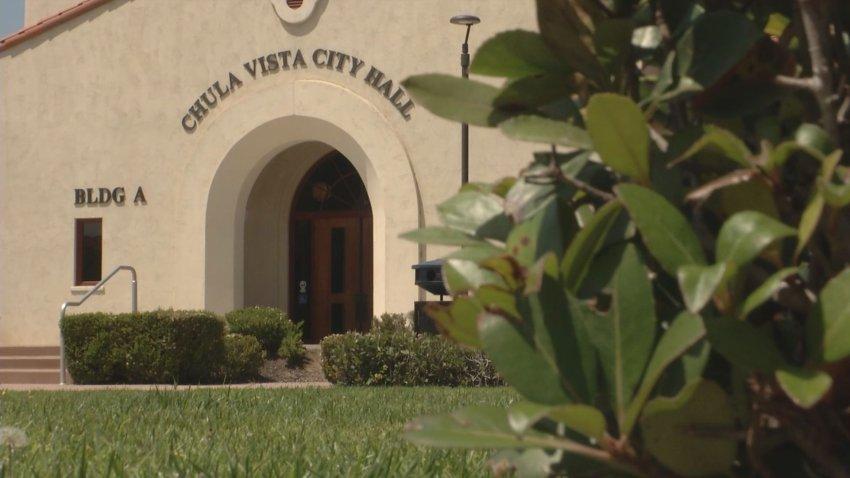 A tan Chula Vista City Hall stands behind a green bush