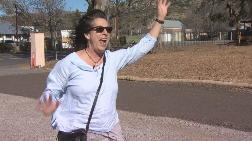 Woman with dark hair and a light colored shirt stands waving her arms in the wind