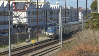 A train passes by a large white factory