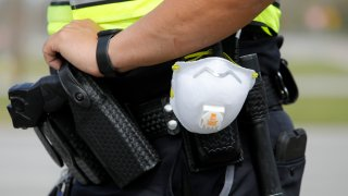 In this March 16, 2020, photo a North Charleston police officer carries a protective mask around his gun belt while working traffic at Roper St. Francis' North Charleston office in North Charleston, S.C.