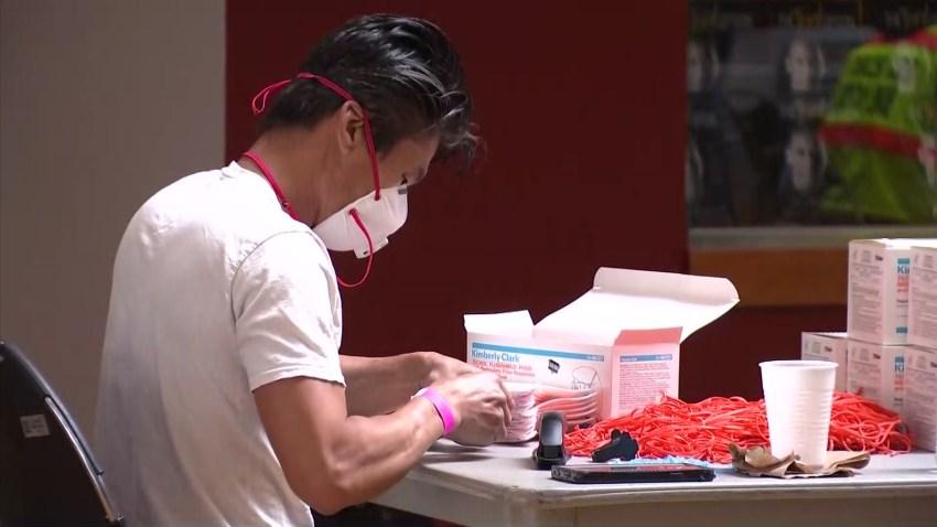 Volunteer repairs straps on defective N95 mask
