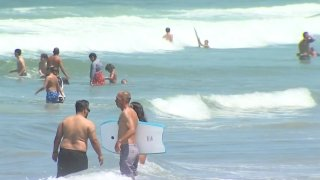 Beachgoers frolic on San Diego shores during the Fourth of July weekend.