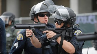 A San Jose Police officer prepares to fire a rubber bullet at a protester.
