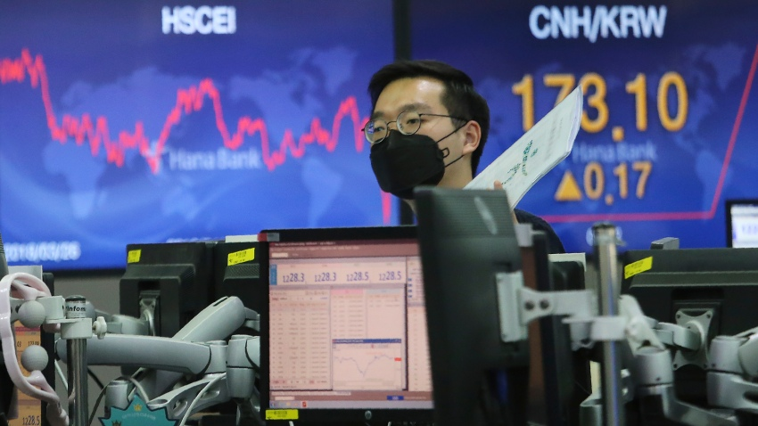 In this April 3, 2020, file photo, a currency trader wearing a face mask works at the foreign exchange dealing room of the KEB Hana Bank headquarters in Seoul, South Korea.