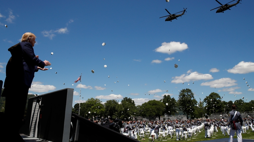 President Donald Trump applauds as Army helicopters fly over and West Point cadets toss their caps into the air at the end of commencement ceremonies on the parade field, at the United States Military Academy in West Point, N.Y., Saturday, June 13, 2020.