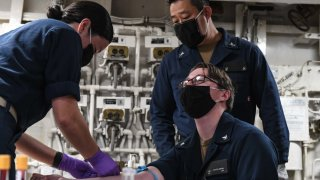 U.S. Navy Lt. j.g. Pamichella Torres, assigned to Naval Hospital Okinawa, left, draws blood from U.S. Navy Hospital Corpsman 3rd Class Shea Ashmore-Scianna, assigned to Naval Hospital Guam, to test for COVID-19 antibodies June 19, 2020. The Theodore Roosevelt Carrier Strike Group is on a scheduled deployment to the Indo-Pacific.