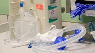 Protective gloves, sanitizer and tubes of a ventilator are pictured