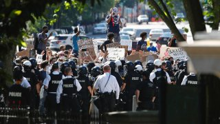 Protesters gather in front of a line of Uniformed U.S. Secret Service as demonstrators gather to protest the death of George Floyd, near the White House, Saturday, May 30, 2020, in Washington. Floyd died after being restrained by Minneapolis police officers.
