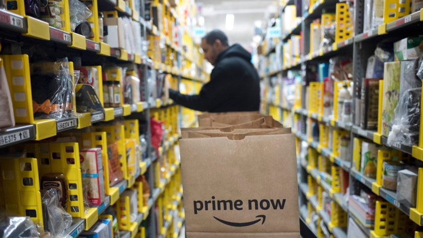 In this Wednesday, Dec. 20, 2017, file photo, a clerk reaches to a shelf to pick an item for a customer order at the Amazon Prime warehouse, in New York.
